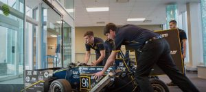University of Toledo Formula SAE members Dustin Moosman, left, and Josh Remmetler, right, push the team's car from last season through the lobby of the North Engineering Building to take a group photo with the car.