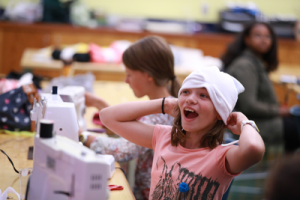 Picture of elementary and middle school students in a sewing workshop